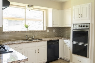 Kitchen with new granite and glass subway backsplash.